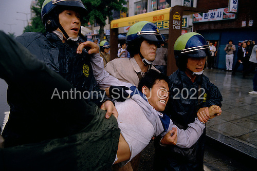 """Seoul, South Korea<br /> May 1987<br /> <br /> Arresting a student protester during a government crackdown on activists.<br /> <br /> After two decades of building an economic miracle, in the summer of 1987 tens of thousands of frustrated South Korean students took to the streets demanding democratic reform. """"People Power"""" Korean-style saw Koreans from all social spectrums join in the protests.<br /> <br /> With the Olympics to be held in South Korea in 1988, President Chun Doo Hwan decided on no political reforms and to choose the ruling party chairman, Roh Tae Woo, as his heir. The protests multiplied and after 3 weeks Chun conceded releasing oppositionist Kim Dae Jung from his 55th house arrest and shaking hands with opposition leader Kim Young Sam. Days later he endorsed presidential elections and an amnesty for nearly 3,000 political prisoners. It marked the first genuine initiative of democratic reform in South Korea and the people had their victory."""