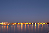 The old Pont de Pierre bridge at night with reflections in Bordeaux on the Garonne River - an ambulance making a blue dotted line on the bridge