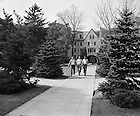 GPHR 45/0038:  Three male students walking on campus with Lyons Hall exterior in the background, 1948-1949.<br /> This photo was published in the 1949 Dome yearbook, page 208. Image from the University of Notre Dame Archives.