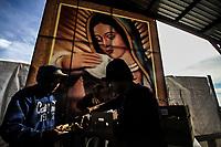 Inmigrante hondureño recibe alimentos en el comedor del migrante en el ejido la victoria.<br /> Imagen de la Virgen de Guadalupe.