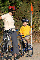 Jill and Josh riding Kona bike with tagalong attached. .Virginia Water , Surrey  Sept 2003..