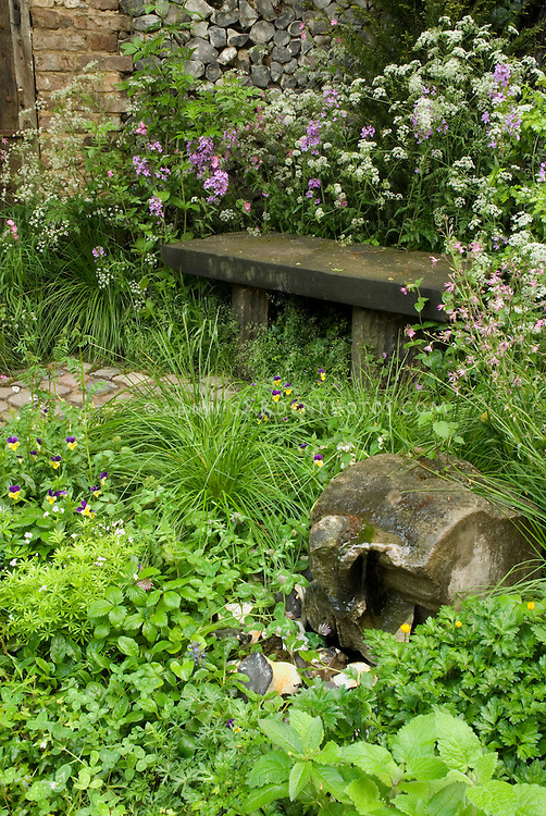 Rustic stone garden bench in old-fashioned grandmother's garden full of plants and flowers, old brick wall