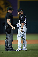 Home plate umpire Sean Cassidy stands in front of Winston-Salem Dash manager Ryan Newman (5) as he yells as Nate Shaver (not pictured) at Truist Stadium on September 17, 2021 in Winston-Salem, North Carolina. (Brian Westerholt/Four Seam Images)