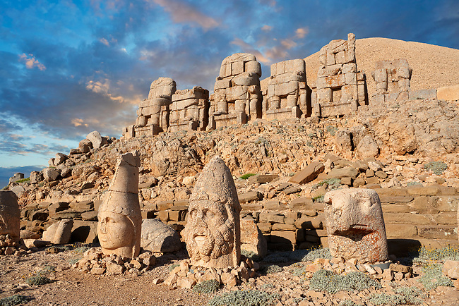 Statue heads at sunset, from right,  Lion, Eagle, Herekles & Apollo,  with headless seated statues in front of the stone pyramid 62 BC Royal Tomb of King Antiochus I Theos of Commagene, east Terrace, Mount Nemrut or Nemrud Dagi summit, near Adıyaman, Turkey