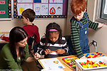 Public elementary school Grade 2 female teacher working with girl on math activity with colored geometric shapes while boy looks on