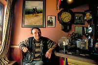 A smiling man relaxes drinking a pint of stout by the bar at the Red Fox Inn located in the Ring of Kerry. Ring of Kerry, Ireland Red Fox Inn.