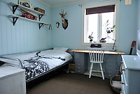 Unlike the rest of the house, the panelling in this boy's bedroom has been painted blue, teamed with steely grey furniture
