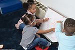 Education Preschool toddler 2s program Head Start two girls and a boy drawing together on dry erase board