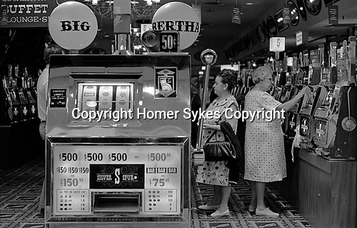 One armed bandits arcade slot machines, women playing  gambling. Big Bertha a giant one arm bandit in a Penny Arcade. 1969, Reno Nevada Casio. USA