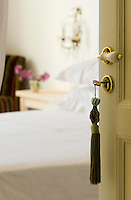 A green tassel hangs from the key to a bedroom