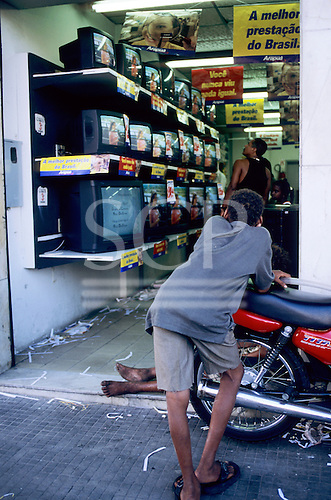 Salvador, Bahia, Brazil. Street kid looking at TV in a shop from the street leaning on a motorbike.