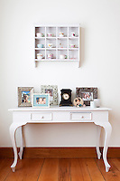 The side table, together with the little shelves above it, is second hand, and displays a collection of family photographs