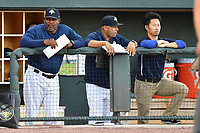 Coaches Jonathan Hurst, Joel Fuentes and trainer Kiyoshi Tada of the Columbia Fireflies watch from the dugout in a game against the West Virginia Power on Friday, May 19, 2017, at Spirit Communications Park in Columbia, South Carolina. West Virginia won, 3-1. (Tom Priddy/Four Seam Images)