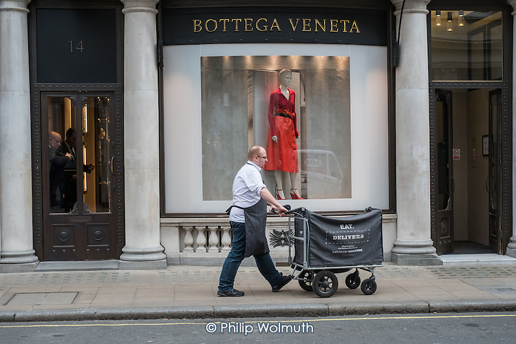 Eat delivery worker outside Bottega Veneta luxury shop, Mayfair, London.