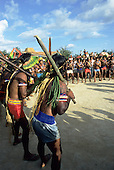Altamira, Brazil. Kayapo Indians in a war dance with borduna clubs wearing feather headdresses.