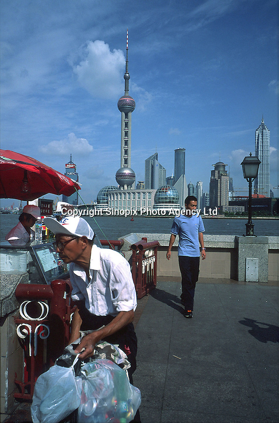 With Pudong's towers in the background, an old man sorts through rubbish bins on the Bund. .04-JUL-01
