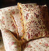 A faded velvet damask cushion combined with one in paisley on a chintz upholstered armchair