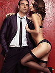 Sexy couple portrait of young man wearing a business suit and a seductive young woman in black lingerie and stockings on red background Image © MaximImages, License at https://www.maximimages.com