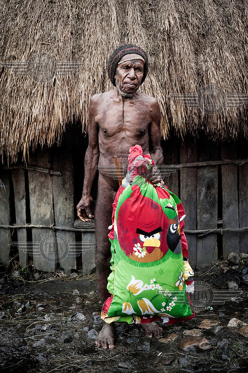 Senaila, who is over 70 years old, holds an 'Angry Birds' pillow near his house. He bought the pillow for 90,000 Rupiah (GBP 4.75) and puts it under his head when sleeping on the floor of his hut.