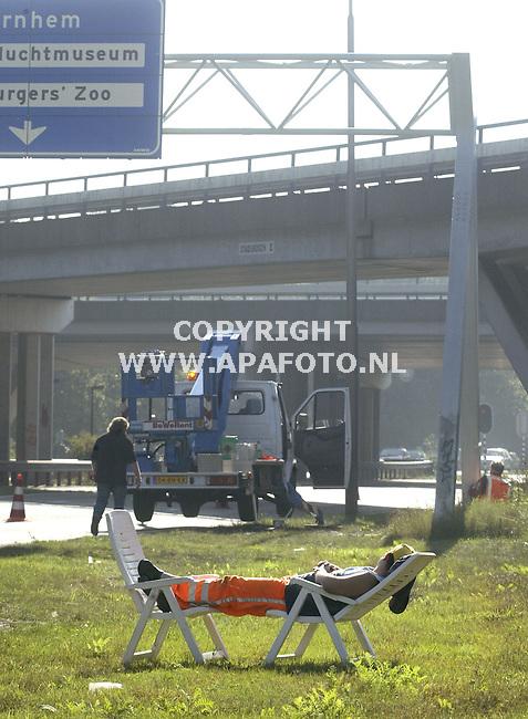 Arnhem, 131005<br /> Wegwerker werkt, in het zonnetje, slaap weg.<br /> Even een dutje in de zon. Een wegwerker van Van der Linden verkeerstechniek<br /> wacht even met het verplaatsen van de pilonnen bij knooppunt Waterberg in<br /> Arnhem. Van der Linden zorgt voor de veiligheid, terwijl schilders van<br /> servicebedrijf Hertel uit Emmen de portalen van de bewegwijzering van een<br /> nieuwe coating voorzien.<br /> Foto: Sjef Prins - APA Foto