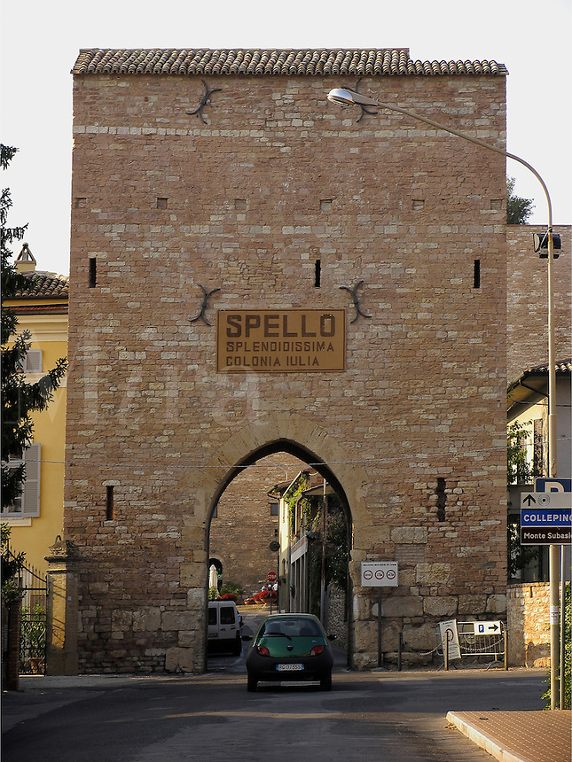 Green compact car enters Porta Consolare city gate to the city of Spello, Ital