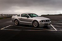 2006 Ford Mustang GT parked at an empty parking lot where it has recently rained with ominous dark clouds overhead.