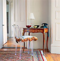 The juxtaposition of old and new: a Philippe Starck Ghost chair and a pretty antique writing table with Bakelite telephone.