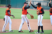 FCL Orioles Orange outfielders Donta' Williams (48) and Colton Cowser (44) high five shortstop Isaac De Leon (51) after a game against the FCL Pirates Gold on August 9, 2021 at Ed Smith Stadium in Sarasota, Florida.  (Mike Janes/Four Seam Images)