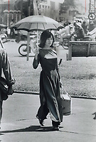 1972 FILE PHOTO - <br /> <br /> Young woman on shopping trip; Umbrella protects her from the hot sun