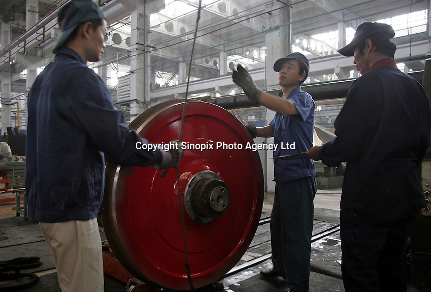 Chinese workers moves a set of locomotive wheels in place for processing at the state-owned Datong Electric Locomotive Co. LTD in Datong, Shanxi Province, China. China's developing economy has created a huge demand for faster and more powerful locomotive engines to move its people and goods within its vast and expanding railway network, the Datong company is currently working together with several western partners including Alstom of France and ABC of the U.S..05 Jul 2005