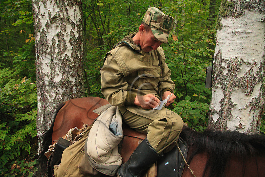 Sabit Galin on horseback, en route for the harvest, stops to fill out a transit form that he puts in a letterbox attached to a tree. All the beekeeper's essentials can be found on Salim's mount: the smoker, the support board, the leather rope for climbing the hundred-year-old pine trees holding the hives.