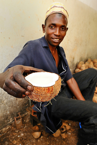 A worker with an open coconut at Coast Coconut Farms, Kenya.   Coast Coconut Farms was started in 2005 by The Pope Foundation as an economic development project with a mission to provide sustainable employment, management and ownership opportunities for the rural people of Kenya