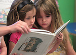 Vivi Mellow, 4, left, and her sister Neva, 5, read before Storytime at the Carson City Library on Wednesday, July 25, 2012. .Photo by Cathleen Allison