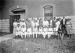 CHURCH GROUP OUTSIDE QUINN CHAPEL, BEFORE 1915. Quinn Chapel African Methodist Episcopal Church was Lincoln's first African American congregation, founded in 1871, just four years after the city was established. The brick and stone church was constructed in 1900 at 1026 F Street. The photograph was taken before the congregation moved the building to Ninth and C Streets in 1915, where the remodeled structure still houses Quinn Chapel in 2008.<br /> <br /> Photographs taken on black and white glass negatives by African American photographer(s) John Johnson and Earl McWilliams from 1910 to 1925 in Lincoln, Nebraska. Douglas Keister has 280 5x7 glass negatives taken by these photographers. Larger scans available on request.