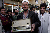Kabul, Afghanistan<br /> November 2001<br /> <br /> A man proudly displays his new radio which he purchased for $30. Now that the Taliban has fled Kabul people are shopping to bring back music and TV which had been banned for 6 years.