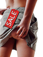 Close up of young women from behind lifting her mini skirt to scratch ber bare bottom. There is a  ticket attached to the skirt with the word Sale on it.