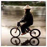 A woman cycling through the streets of Jakarta during a rainstorm.