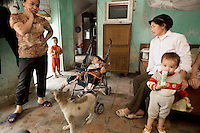 Vietnam. Ha Tay province. Lai Xa. House of the Dinh's family. Mother and children, a dog, an educationally subnormal  (mentally handicapped) boy lied down in a child's push-chair, a television and a bed. Lai Xa is a typical hamlet (village) and is part of the Kim Chung commune located 15 km west of Hanoi. 07.04.09© 2009 Didier Ruef