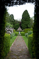 A small pavillion can be found at the end of an overgrown stone path, flanked by flowerbeds and topiary