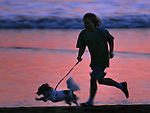 A boy and his dog runs on Rodeo Beach at Fort Chronkite in California during sunset.