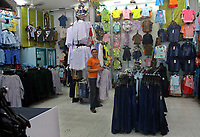 A Palestinian man sills clothes in his shop in the market in Gaza City, Wednesday, Aug. 29, 2007. (FADY ADWAN)