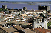Ancient city walls and roof tops with  Notre Dame des Sablons in view, Aigues-Mortes, France.