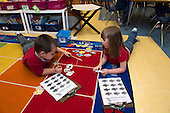 "MR / Schenectady, NY. Zoller Elementary School (urban public school). Kindergarten inclusion classroom. Students play ""go fish"" game at math learning center time. Left: boy, 5; Right: girl, 6. MR: Gia3, Bin1. ID: AM-gKw. © Ellen B. Senisi."
