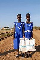 UGANDA, Karamoja, Karimojong tribe, children going home from school by walking, two girls in blue schooluniform with Unicef plastic bag for books