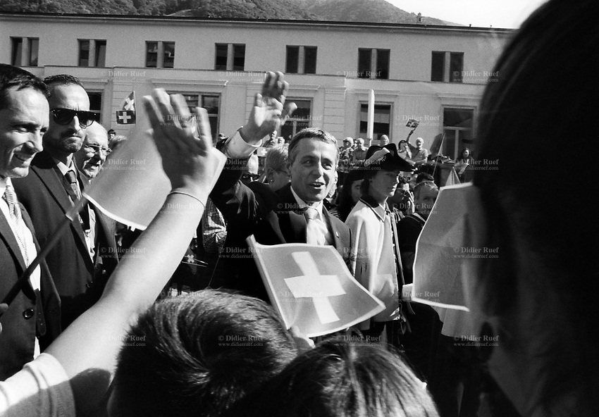 Switzerland. Canton Ticino. Bellinzona. A warm welcome by the crowd to the newly-elected member of the Swiss cabinet, Ignazio Cassis, who will take over the foreign ministry. He is affiliated to the FDP The Liberals and was elected to the Federal Council of Switzerland on 20 September 2017. Ignazio Cassis is greeting the crowd with his right hand on his first return to Canton Ticino. The Canton Ticino has waited eighteen years for a newly elected minister at the Federal Council of Switzerland. The last one was Flavio Cotti (third man from the left) who was elected on 10 December 1986 and handed over office on 30 April 1999. He is affiliated to the Christian Democratic People's Party of Switzerland. The flag of Switzerland consists of a red flag with a white cross (a bold, equilateral cross) in the centre. It is one of only two square sovereign-state flags. 28.09.2017 © 2017 Didier Ruef