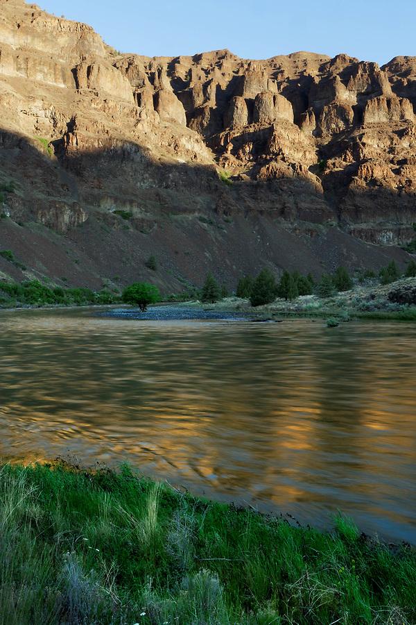 Basalt cliffs reflected on John Day River at sunrise, central Oregon desert, Oregon, USA