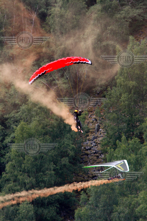 Hang glider and parachute jumper fly near Gudvangen. The Extremesport Week, Ekstremsportveko, is the worlds largest gathering of adrenalin junkies. In the small town of Voss enthusiasts in a varitety of extreme sports come togheter every summer to compete and play.© Fredrik Naumann