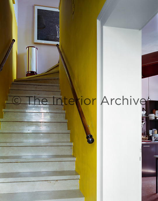 Concrete steps enhanced with yellow-painted walls and a traditional mahogany handrail lead to the upper floor of the apartment
