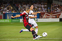 Djamel Mesbah (15) of A. C. Milan clears the ball away from Mesut Ozil (10) of Real Madrid. Real Madrid defeated A. C. Milan 5-1 during a 2012 Herbalife World Football Challenge match at Yankee Stadium in New York, NY, on August 8, 2012.