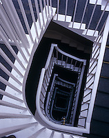 View looking down the back stairs with its simple white wooden balustrade